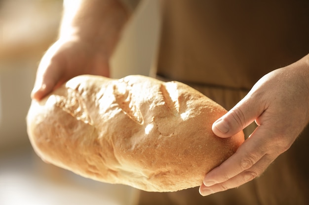 Male chef with loaf of bread, closeup
