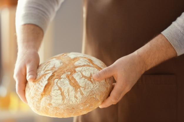 Male chef with loaf of bread in kitchen, closeup