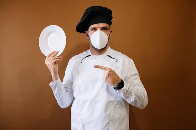 マスクと空のプレートを持つ男性シェフ