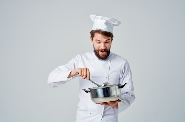 Male chef with a saucepan in his hands cooking food working in a restaurant