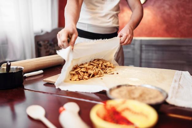 男性シェフがフィリングを生地に包み、リンゴのシュトルーデル準備プロセス。自家製の甘いデザート