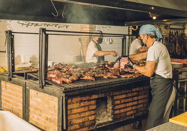 Повара-мужчины в масках и сетках для волос готовят мясо на гриле и используют щипцы для мяса.