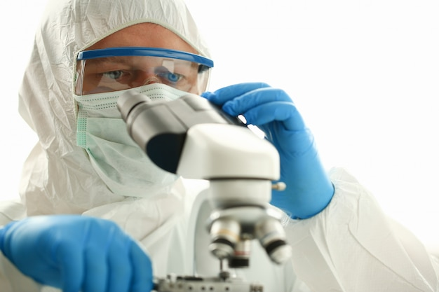 Male chemist in blue protective gloves look
