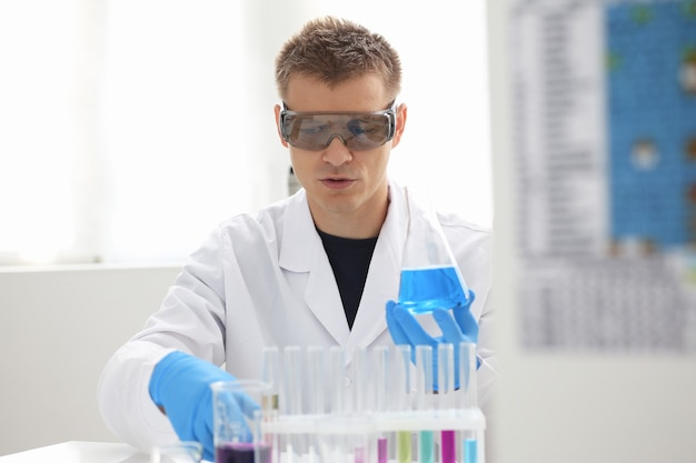 A male chemist holds test tube of glass in his hand overflows a liquid solution of potassium permanganate conducts an analysis reaction