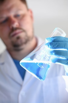 A male chemist holds test tube of glass in his hand overflows a liquid