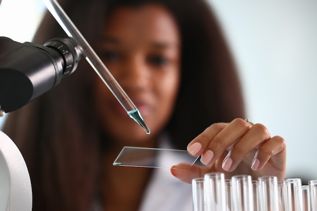 A male chemist holds test tube of glass