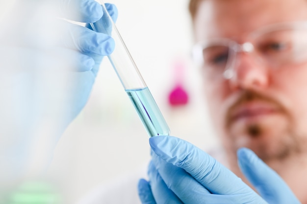 A male chemist holds test tube of glass in