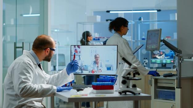 Мужской химик, слушая профессионального врача по видеосвязи, обсуждает во время виртуальной встречи в медицинской исследовательской лаборатории. ученый изучает эволюцию вакцины с использованием высокотехнологичных исследований лечения