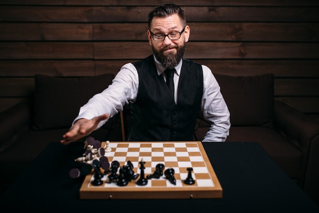 Male chess player has win the game and threw all the pieces.