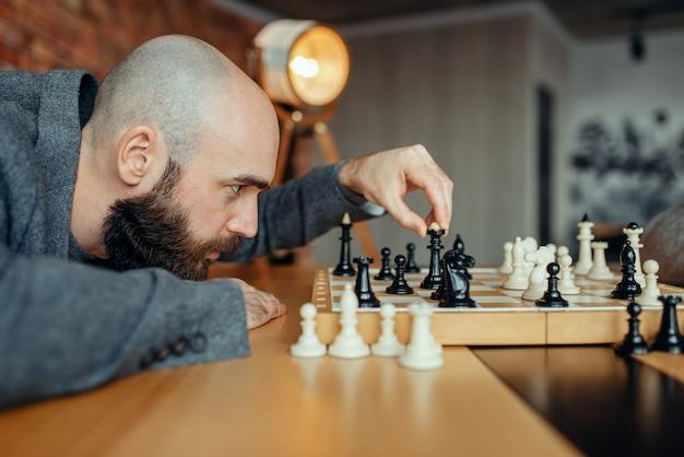 黒い数字を演奏する男性のチェスプレーヤー、女王の動き。取締役会でのチェスプレーヤー、屋内での知的トーナメント。木製テーブルのチェス盤、戦略ゲーム