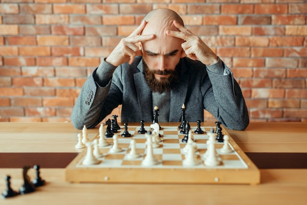 Male chess player playing black figures, thinking process.