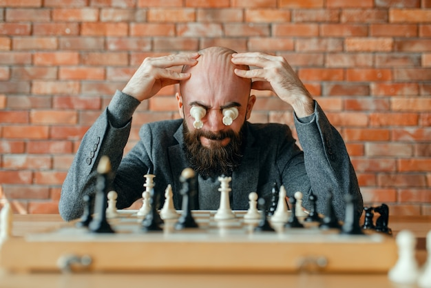 Male chess player with figures in the eyes, thinking process.