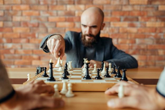 手に白い図、女王の動きを持つ男性のチェスプレーヤー。