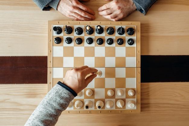 Шахматисты мужского пола на доске, ход белых, вид сверху. двое шахматистов начинают интеллектуальный турнир в закрытом помещении. шахматная доска на деревянном столе