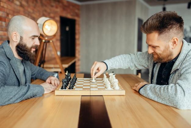 Шахматисты-мужчины начинают игру, первый ход. двое шахматистов начинают интеллектуальный турнир в закрытом помещении. шахматная доска на деревянном столе, стратегическая игра