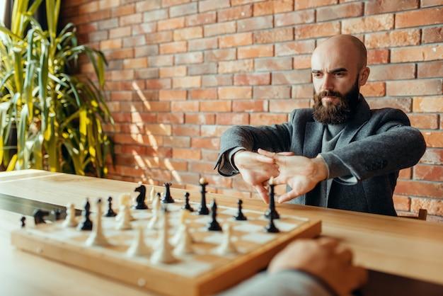 Шахматисты мужского пола на соревновании, доска с фигурами.
