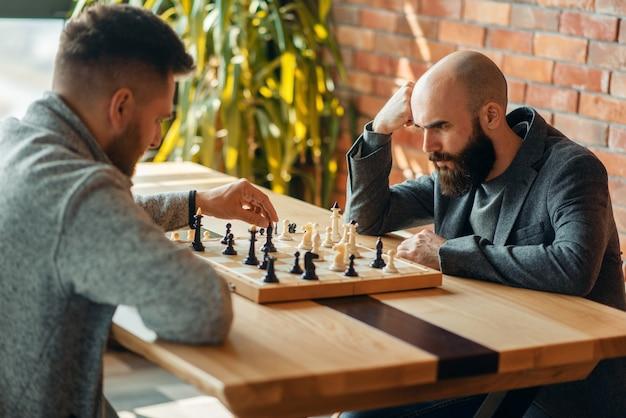 Шахматисты-мужчины, играющие за доской, перемещают черного слона.