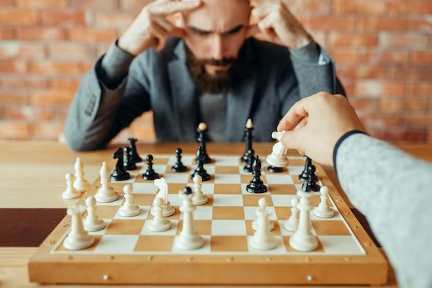 Шахматисты-мужчины играют за доской, ход белым конем. двое шахматистов начинают интеллектуальный турнир в закрытом помещении. шахматная доска на деревянном столе