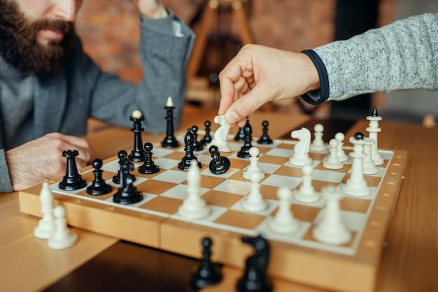 Шахматисты мужского пола играют за доской, белый конь берет пешку. двое шахматистов начинают интеллектуальный турнир в закрытом помещении. шахматная доска на деревянном столе