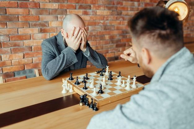 Шахматисты мужского пола играют за доской, белые выигрывают, мат.