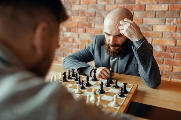 Мужские шахматисты играют, мыслительный процесс
