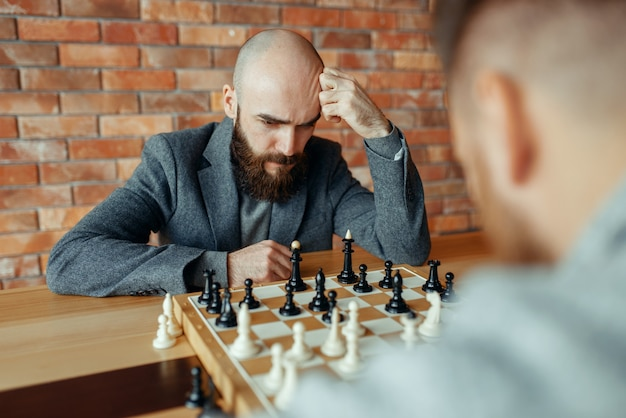 Male chess players playing, thinking process.
