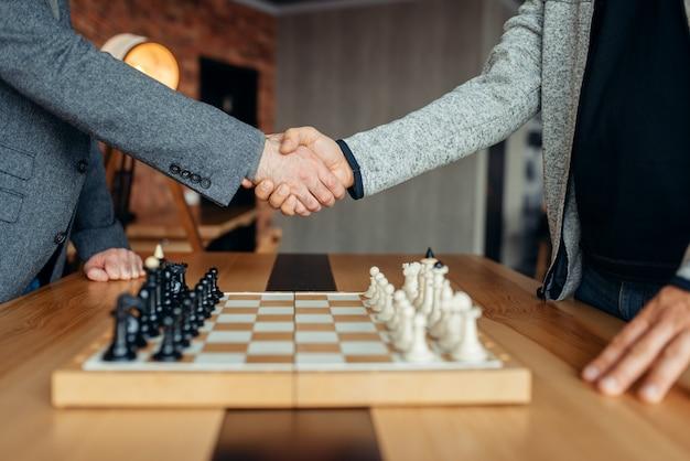 Шахматисты-мужчины пожимают друг другу руки перед игрой