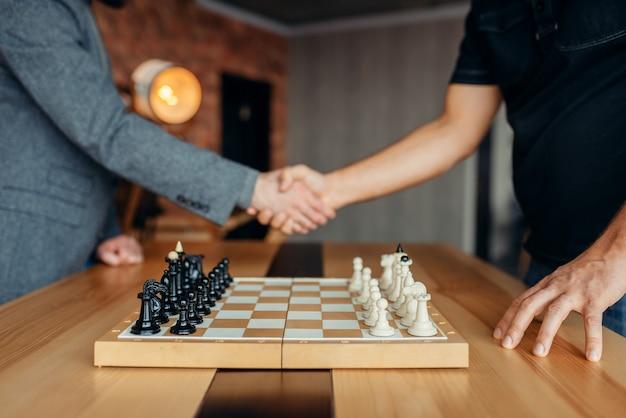 Шахматисты-мужчины обмениваются рукопожатием перед игрой.