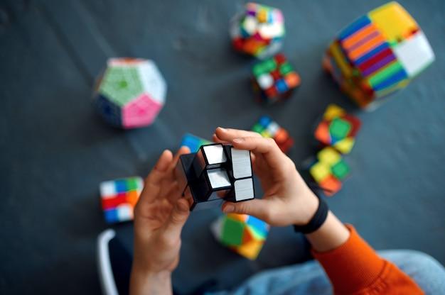 Дети мужского пола играют с кубиками головоломки. игрушка для тренировки мозга и логического мышления, творческой игры, решения сложных задач.