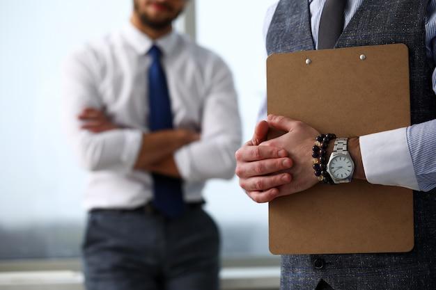 Мужской клерк руку в костюме и галстуке с бумагой обрезается на подушку