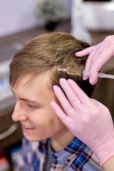 남성 고객은 머리에 주사를 맞습니다. 남성의 탈모와 싸우고 있습니다. 인식 할 수없는 여성 미용사 손 trichologist와 머리 클로즈업. 주사기에 집중