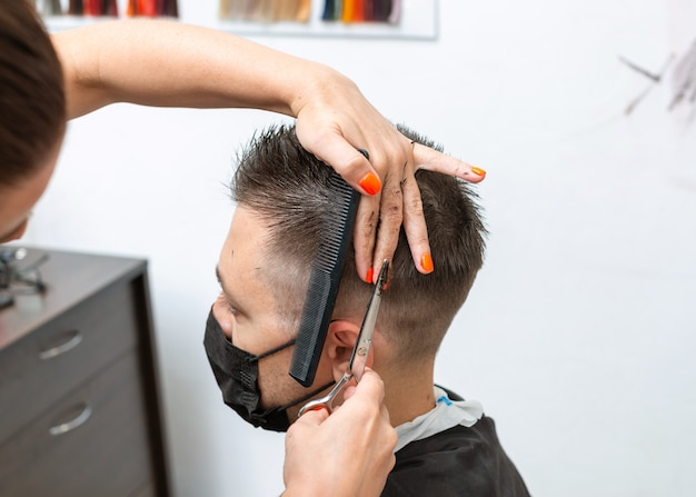 コロナウイルスのパンデミック中にマスクを着用して散髪をしている男性のクライアント。ヘアハサミで作業している床屋の手の写真をクローズアップ。