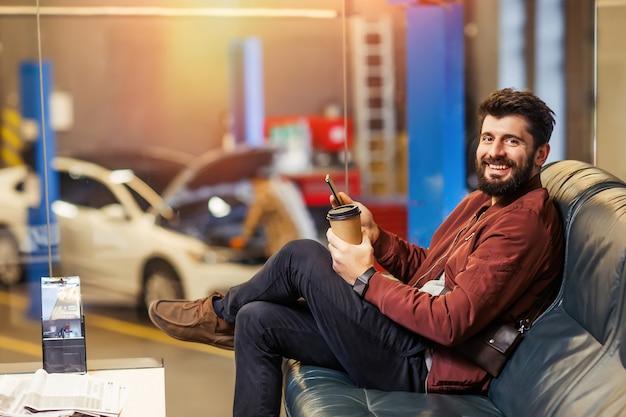 ワークショップで彼の車を待っているとカメラを見ている男性のクライアント