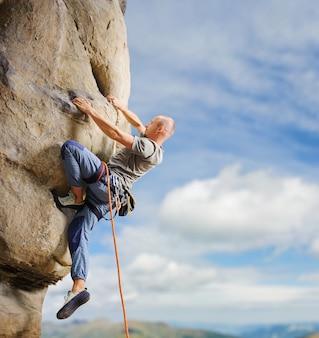 밧줄으로 자연에서 큰 볼더를 등반하는 남성 산악인