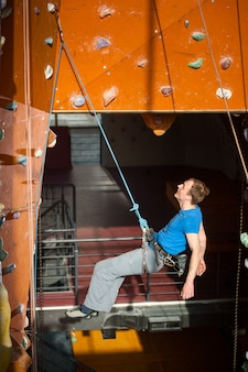 Male climber hanging on a rope an indoor rock-climbing wall