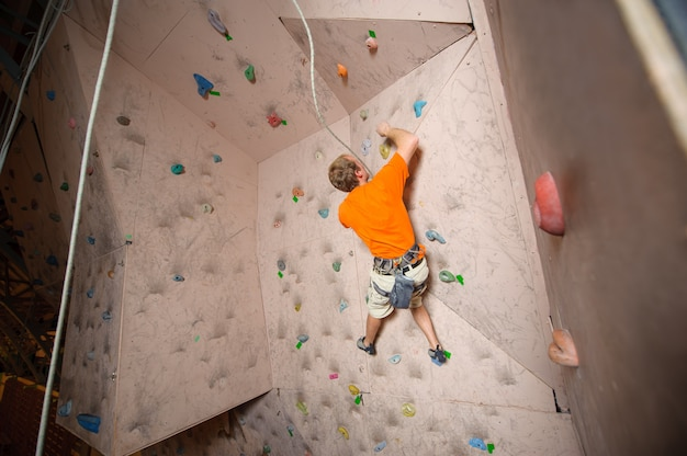 Male climber practicing rock-climbing on a rock wall indoors