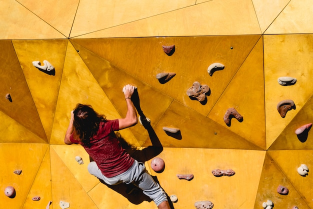 Male climber trying a complicated route to the sun on an outdoor climbing wall