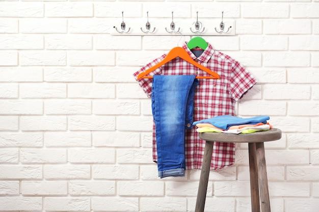 Мужская одежда на вешалках в комнате