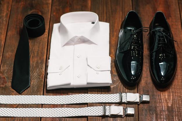Комплект мужской одежды. рубашка галстук обувь и подтяжки на деревянном столе