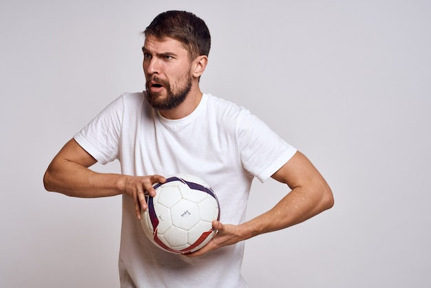 Male coach with a soccer ball in his hands on a light