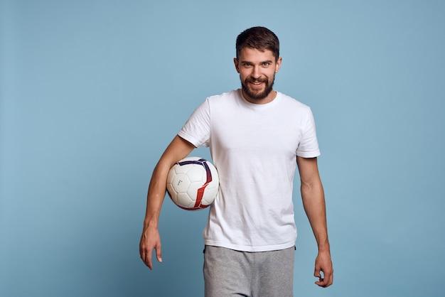 Мужской тренер с футбольным мячом на синем