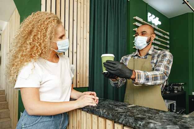 Male coffee shop worker giving ready order to the client wearing face mask, coronavirus concept
