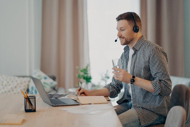 Male college student listens academic podcast sits at desk with laptop consults client by video makes notes drinks water from glass watches webinar dressed in checkered shirt poses at home office