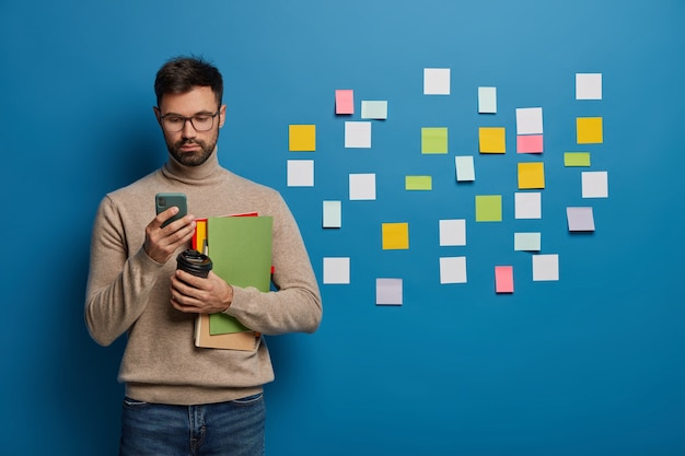 Male college student uses mobile phone for online chatting, drinks takeout coffee, holds notepads or textbooks, prepares for lesson, stands behind blue wall with many sticky notes