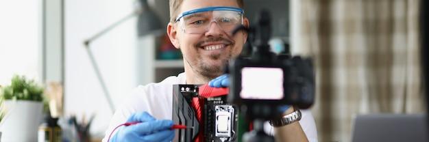 男性のコンピューター修理工がビデオレッスンを録画しています
