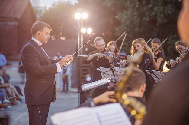 Мужской дирижер, руководящий выступлением оркестра на улице