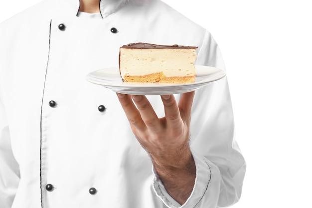 Мужской кондитер с вкусным десертом на белом, крупным планом