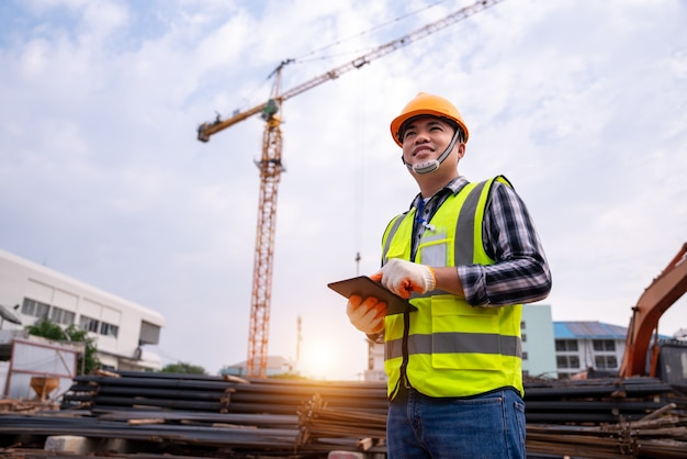 Male construction engineer. architect with a tablet computer at a construction site. asian young man looking, building site place. construction or building engineer concept