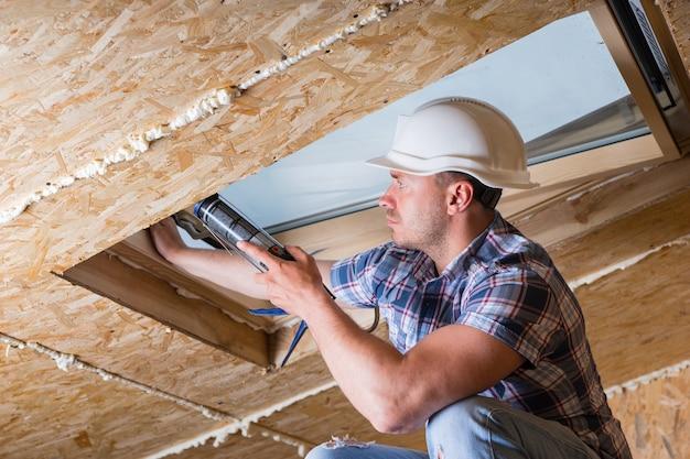 미완성된 집의 천장에 채광창에 신선한 코킹을 적용하는 남성 건설 노동자 빌더