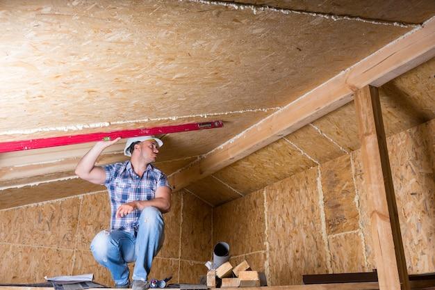 노출된 합판 파티클 보드가 있는 미완성 주택의 천장 등급을 측정하기 위해 빨간색 레벨을 사용하여 높은 비계에 웅크리고 있는 남성 건설 노동자 빌더